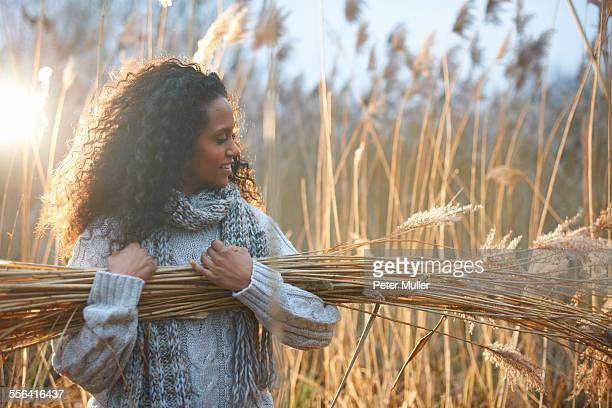Woman carrying bundle of wheat