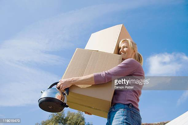 Woman carrying cardboard boxes