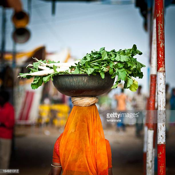 Woman carrying carrots on her head in Pushkar