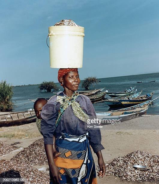Woman carrying child on back and bucket of fish on head, portrait