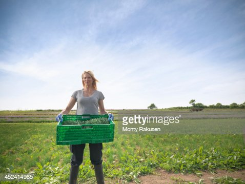 Woman carrying crate of chives