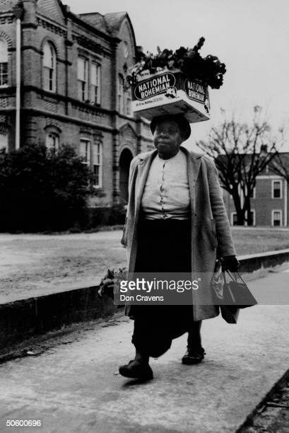 Woman carrying crate of turnip greens on her head walking during bus boycott protesting policy of forcing African Americans to ride at the back of...
