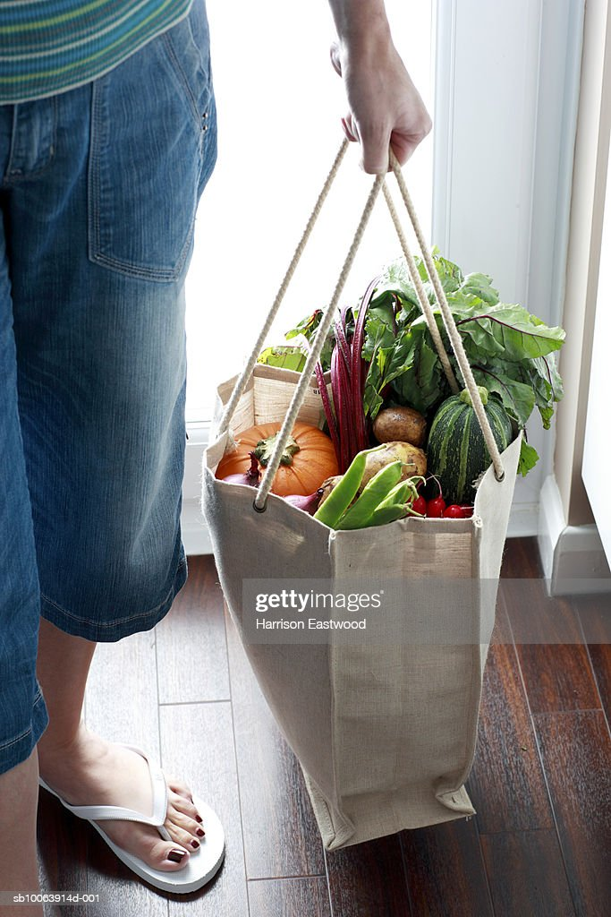 Woman carrying eco friendly shopping bag full of vegetables, low section : Stock Photo