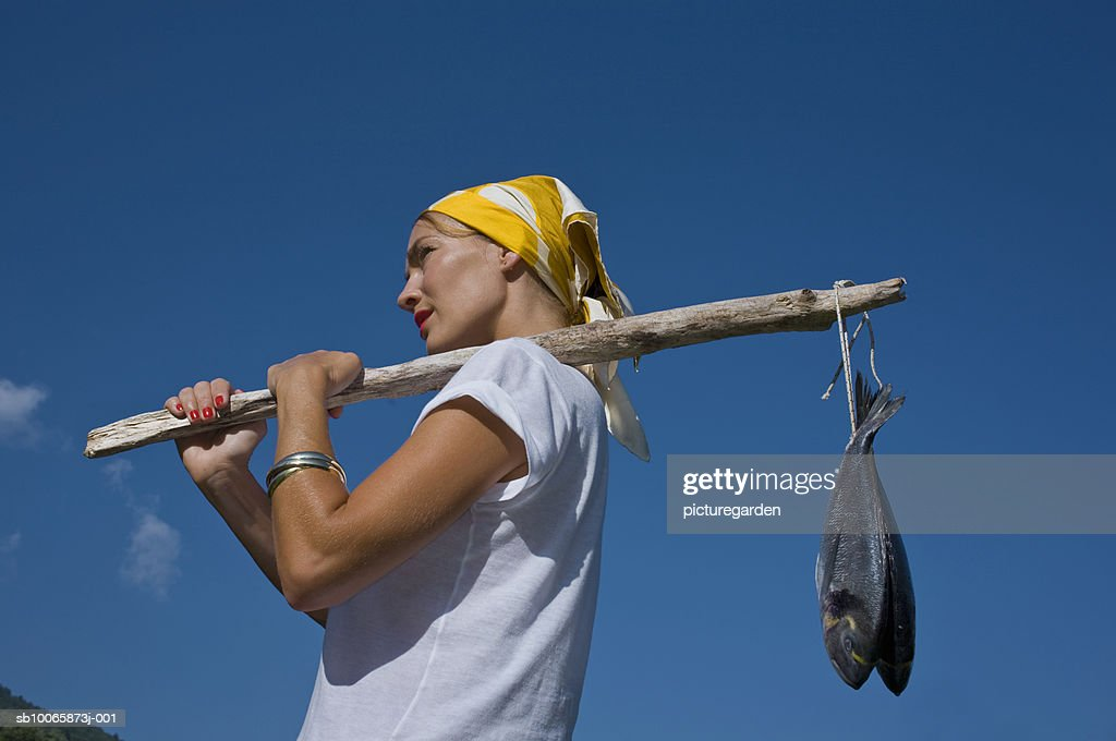 Woman carrying fish, low angle view