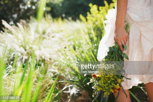 Femme portant des fleurs dans le jardin photo getty images for Fleurs dans le jardin