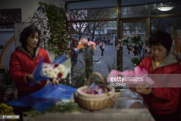 A woman carrying flowers walks on a street as vendors prepare flowers for Mother's Day at a flower shop in Pyongyang on November 16 2017 North...