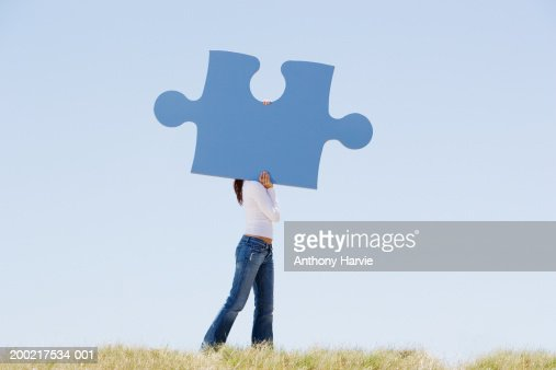 Woman carrying giant jigsaw piece, obscuring face, side view : Stock Photo
