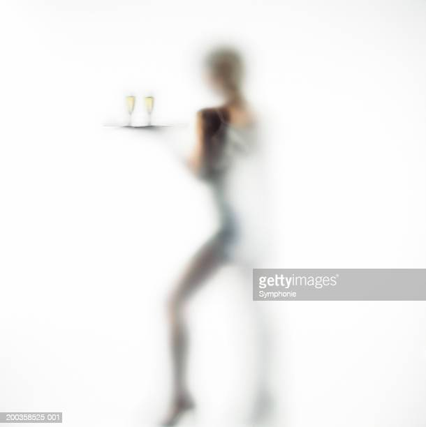 Woman carrying glasses of wine on tray, rear view(defocussed)