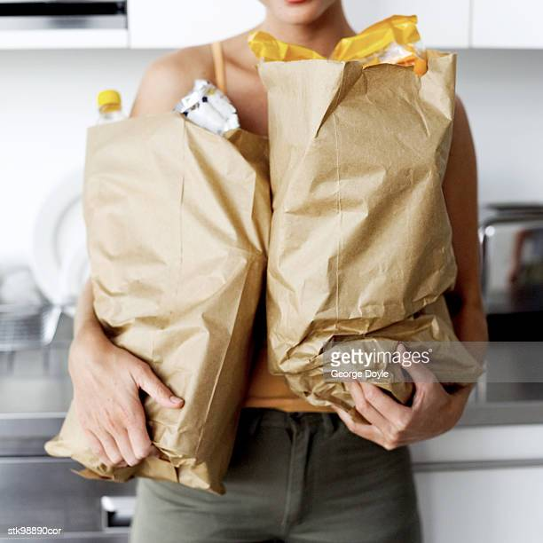 woman carrying groceries in a brown paper bag
