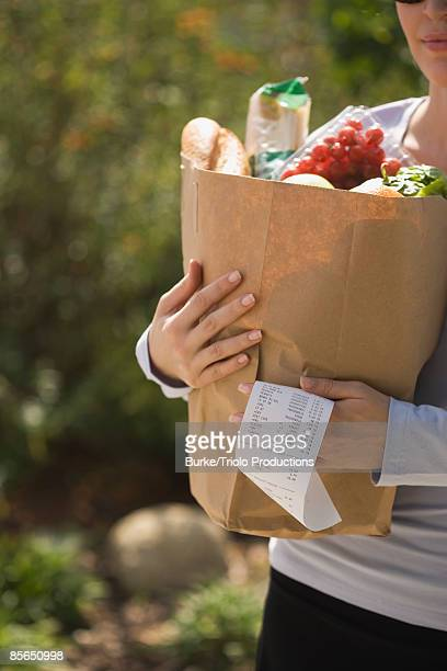 Woman carrying grocery bag and receipt