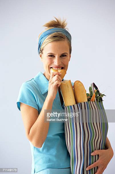 Woman carrying grocery bag, eating baguette