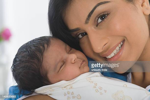 Woman carrying her baby and smiling
