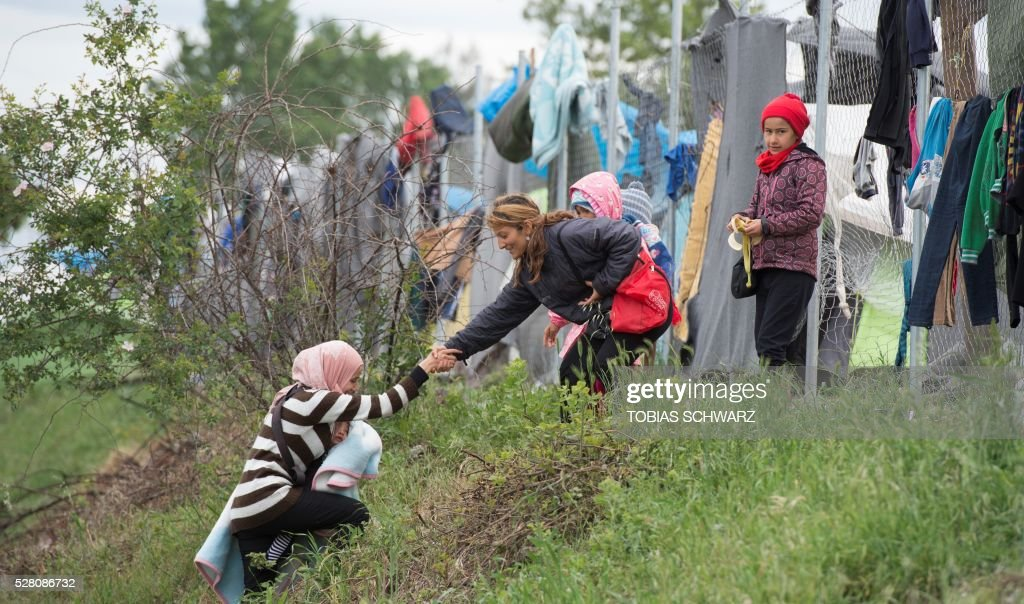 A woman carrying her baby is helped up a slope at a makeshift camp for migrants and refugees near the village of Idomeni not far from the Greek-Macedonian border on May 4, 2016. Some 54,000 people, many of them fleeing the war in Syria, have been stranded on Greek territory since the closure of the migrant route through the Balkans in February. / AFP / TOBIAS