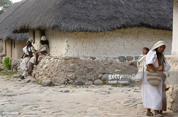 A woman carrying her baby on her back walks past two men dressed in white serapes tall coned hats hold Poporos in their hands while hanging around...