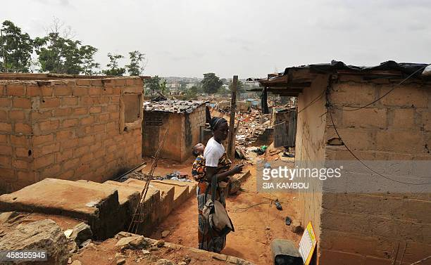 A woman carrying her baby stands in a street of the Washington slum of Abidjan's rich Cocody district during its demolition on February 4 2014 The...