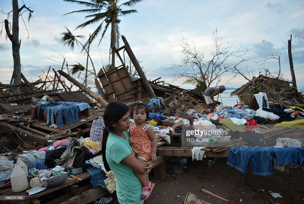 A woman carrying her child stands next to their destroyed house in Boston town, Davao Oriental province on December 11, 2012. The United Nations launched a 65 million USD global appeal on December 10 to help desperate survivors of a typhoon that killed more than 600 people and affected millions in the southern Philippines.