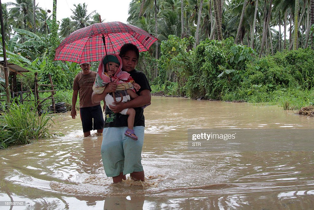 A woman carrying her child wades through a flooded road brought about by heavy rains due to Typhoon Bopha, as she evacuates to a safer place, in Pantukan town, Compostela Valley province, in southern island of Mindanao on December 4, 2012. Typhoon Bopha killed 43 people in one hard-hit Philippine town December 4, local television station ABS-CBN reported from the scene. AFP PHOTO