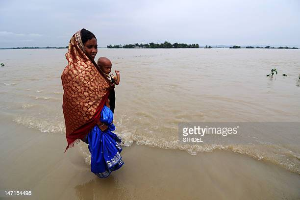 A woman carrying her child walks along a road submerged in floodwaters at Ashigarh village in Morigoan district about 80 kms from Guwahati the...