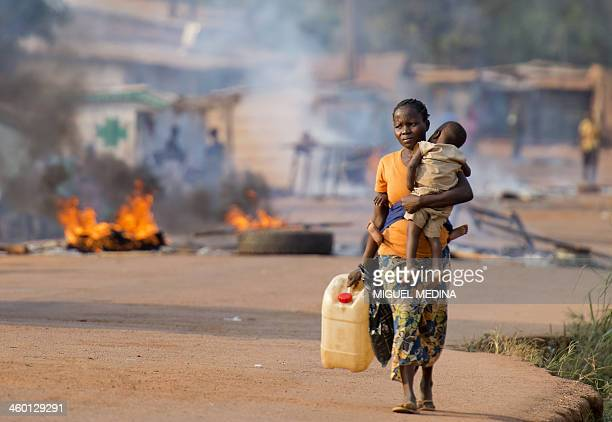 A woman carrying her child walks past the Cocoro market in the PK5 district of Bangui on January 2 2014 after members of the Muslim community burned...