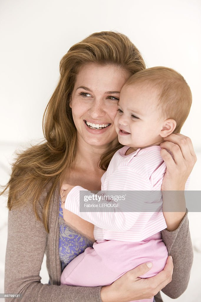 Woman carrying her daughter and smiling : Stock Photo