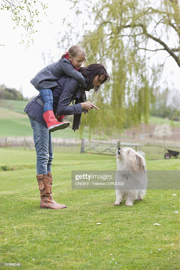 Woman carrying her daughter on piggyback and scolding her dog : Stock Photo