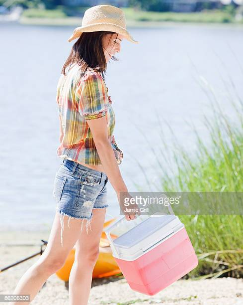 Woman carrying ice chest on beach