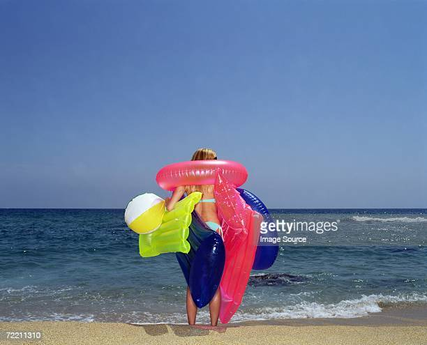 Woman carrying inflatable toys on beach