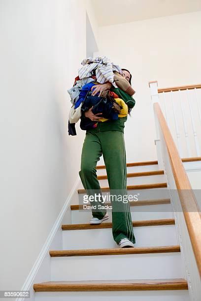Femme transportant des escaliers de blanchisserie