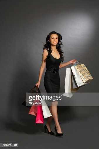 Woman carrying multiple shopping bags : ストックフォト