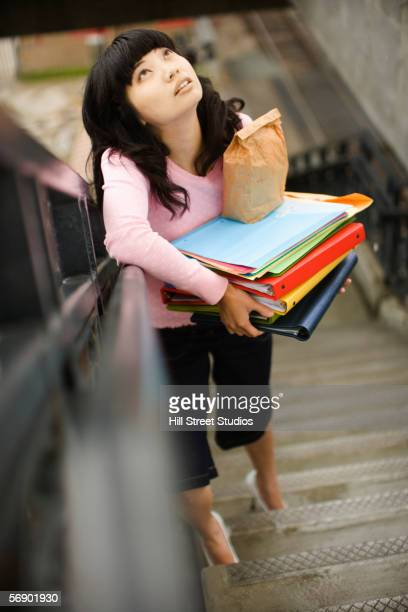 Woman carrying notebooks upstairs