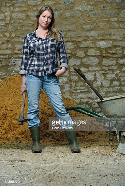 Woman carrying pickaxe in yard