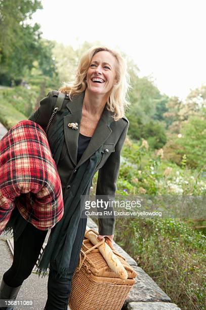 Woman carrying picnic basket in park