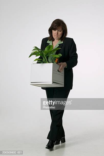 Woman carrying plant in carton, in studio