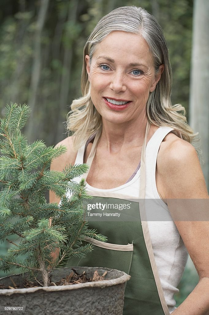 Woman carrying potted tree : Stock Photo