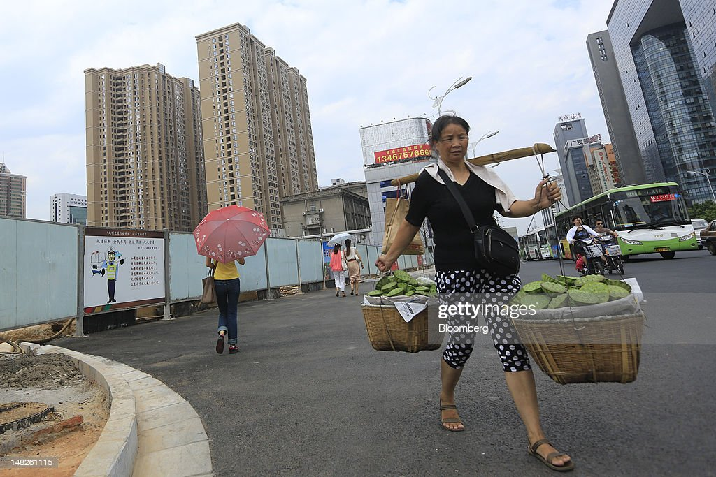 A woman carrying produce for sale walks past newly built residential housing in Changsha, Hunan Province, China, on Friday, July 13, 2012. Gross domestic product (GDP) expanded 7.6 percent in the second quarter of 2012 from a year earlier, China's National Bureau of Statistics said today in Beijing. Photographer: Nelson Ching/Bloomberg via Getty Images