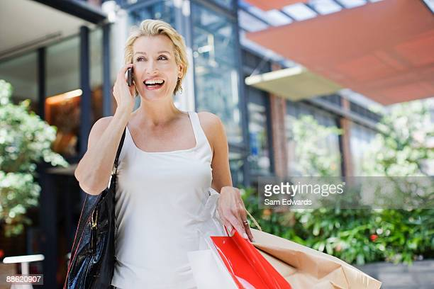 Woman carrying shopping bags and talking on cell phone