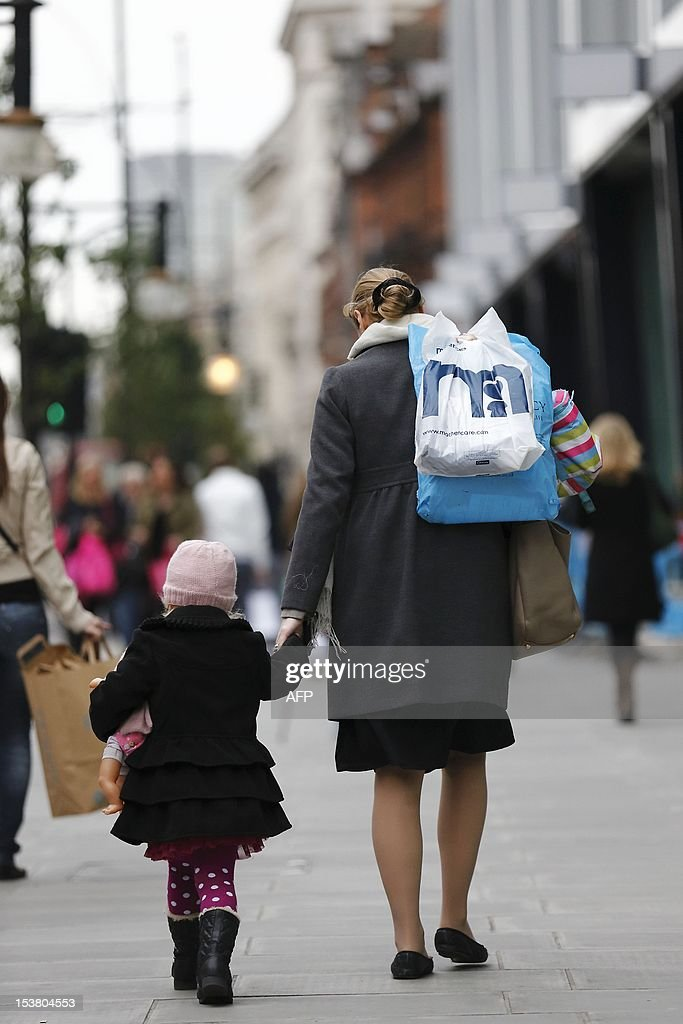 A woman carrying shopping bags of her shoulder walks with her child along Oxford Street in Central London on October 9, 2012. The International Monetary Fund announced it expects the British economy to shrink by 0.4% this year, compared with its forecast of 0.2% growth in July.