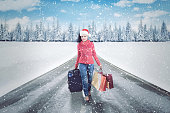 Picture of a beautiful woman carrying shopping bags and suitcase while walking on the road. Shot at winter time