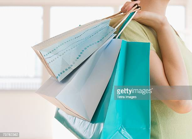 Woman carrying shopping bags over shoulder