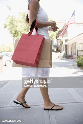 New Young Woman Wearing Red Dress With Shopping Bags Outside