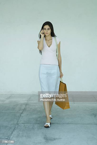 Woman carrying shopping bags, using cell phone, full length portrait