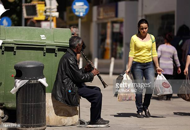 A woman carrying shopping bags walks past a man playing the clarinette on Nicosia's Ledra street on March 20 2013 Cypriot Finance Minister Michalis...