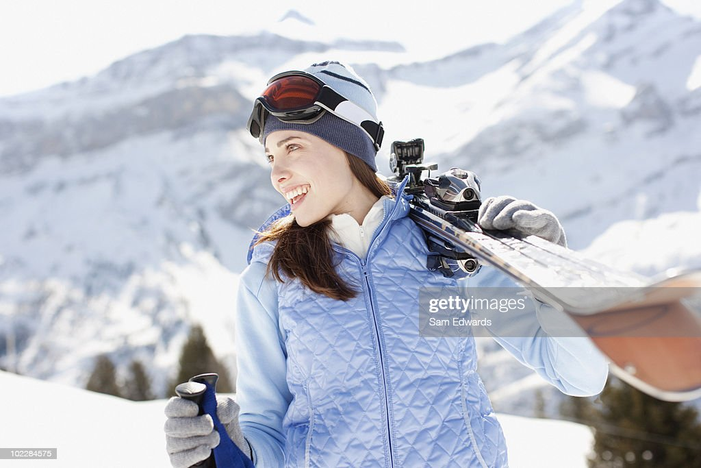 Woman carrying skis : Stock Photo
