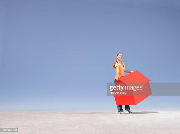 Femme porter petite maison témoin dans le désert