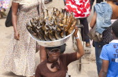 CONTENT] A woman carrying smoked fish in a container on her head amidst a busy market scene Agobogbloshie Market Accra Ghana