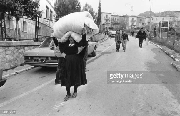 A woman carrying some of her belongings on her head after an earthquake in Southern Italy