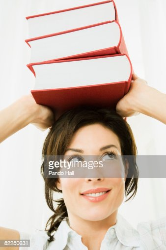 Woman carrying stack of books on head
