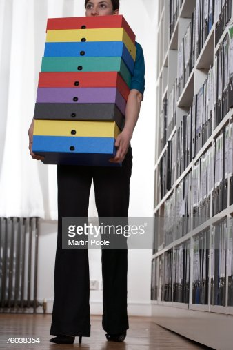 woman carrying stack of coloured box files in office stock photo boxes stack office file