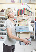 Woman carrying stack of shoe boxes in store