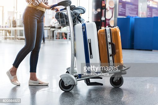 Woman carrying suitcases across hall of airport : Stock Photo